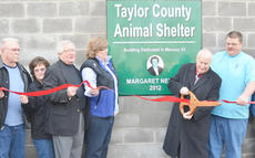"""<div class=""""source"""">Calen McKinney</div><div class=""""image-desc"""">Richard """"Dick"""" Nelson, at right, cuts the ribbon at Taylor County Animal Shelter's new building. The building is dedicated to his wife, the late Margaret Nelson, who loved animals and left the shelter nearly $45,000 in her will. Beside Nelson is Taylor County Animal Shelter Director John Harris.</div><div class=""""buy-pic""""><a href=""""/photo_select/25319"""">Buy this photo</a></div>"""