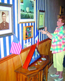 """<div class=""""source"""">Ron Benningfield</div><div class=""""image-desc"""">Ruby Heady adjusts a picture frame that is part of her home memorial to her father, Roy E. McDowell, who died fighting in France in 1944.</div><div class=""""buy-pic""""><a href=""""http://web2.lcni5.com/cgi-bin/c2newbuyphoto.cgi?pub=029&orig=Ruby%2BHeady%2Bhome.jpg"""" target=""""_new"""">Buy this photo</a></div>"""