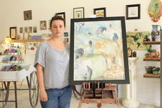 """<div class=""""source"""">Bobbie Lanham</div><div class=""""image-desc"""">Amber Gardner, owner of ArtGypsy in Hodgenville, stands by her watercolor """"A Murder and a Birth,"""" of crows and a fawn.</div><div class=""""buy-pic""""><a href=""""/photo_select/42266"""">Buy this photo</a></div>"""