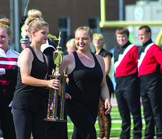 "<div class=""source"">Submitted photo</div><div class=""image-desc"">From left, Kayleigh Warren and Morgan Humphrey, members of the Band of Hawks colorguard, carried the trophy from the field.</div><div class=""buy-pic""></div>"