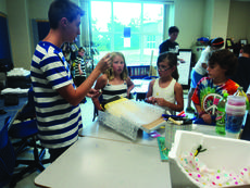 """<div class=""""source"""">submitted photo</div><div class=""""image-desc"""">Camp Intern Andrew Coy poses a question about their invention to campers Harper Hynes, Brenna Southwood, and Gabe Fortier at the 2013 camp. </div><div class=""""buy-pic""""><a href=""""/photo_select/35815"""">Buy this photo</a></div>"""