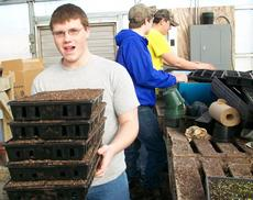 """<div class=""""source""""></div><div class=""""image-desc"""">Nathan Atwell carries trays filled with planting soil while Ben Tucker and Caleb Whelan fill more trays.</div><div class=""""buy-pic""""><a href=""""/photo_select/13229"""">Buy this photo</a></div>"""