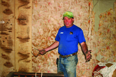 """<div class=""""source"""">Linda Ireland</div><div class=""""image-desc"""">Greg Ballard seems overwhelmed at the amount of things inside the old log house.</div><div class=""""buy-pic""""><a href=""""/photo_select/27548"""">Buy this photo</a></div>"""