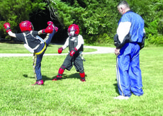 """<div class=""""source"""">Submitted photo</div><div class=""""image-desc"""">Randall Sallee Jr., right, observes Xander Perkins, 6, far left, and Reed Phelps, 7, as they practice their competitive sparring techniques.</div><div class=""""buy-pic""""><a href=""""/photo_select/30521"""">Buy this photo</a></div>"""