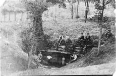 """<div class=""""source"""">Photo courtesy of Carl Howell</div><div class=""""image-desc"""">This is the Sinking Spring in 1895 before the retaining wall and stone steps were added for tourists' safety and access and to prevent erosion. Austin Gollaher, the man postioned in front holding the cane, lived another three years and was believed to be 92 at his death in 1898.</div><div class=""""buy-pic""""><a href=""""/photo_select/26943"""">Buy this photo</a></div>"""