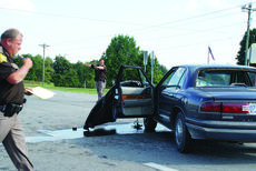 """<div class=""""source"""">Photo by Linda Ireland</div><div class=""""image-desc"""">LaRue County Deputy Russell McCoy directed traffic while Deputy RobbyBrownfield, left, worked on a report after two cars collided at the Ky. 210 crossroads.</div><div class=""""buy-pic""""><a href=""""/photo_select/30240"""">Buy this photo</a></div>"""