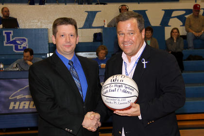 Hawks basketball coach Paul Childress was honored for his 100th win, a 75-57 victory over Caverna on Dec. 16. LaRue County High School Principal Paul Mullins, right, presented the game basketball to him.