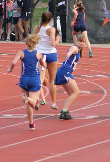 Amanda Brewer hands off the baton to Nichole Thomas during the State Track Meet held at University of Louisville in May.