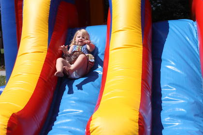 London Jane Greenwell goes down a bouncy slide in the Astro Jump Inflatables kids area on Saturday.