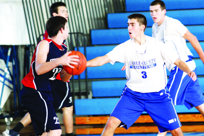 Junior guard Thomas Harmon blocks a shot during intramural play Friday during Blue and White Night. Fans got a glimpse of the Hawks and Lady Hawks basketball teams during the event. Junior Tyler Howell is at right.