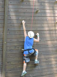 Tommy Wilmoth climbing the rock wall at high ropes.