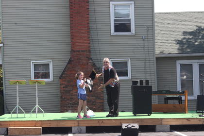 Maddie Riggs, 8, helps perform a trick at the Mr. Magic magic show.