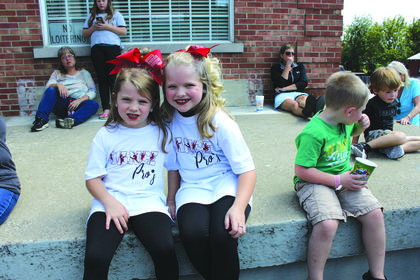 Taylor Holt, 8, sits with her sister Kenadie, 5 waiting for the parade to begin.
