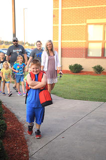 First grader Crayton Thompson walks into HES with his arms crossed.