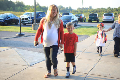First grader Bryce Hutcherson walks into school (HES) for his first day back.