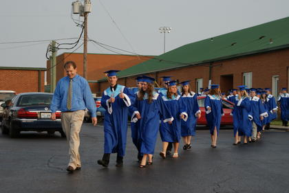 Senior class adviser Rex Hanson leads the graduates to the gym as valedictorian Andrew Skaggs gives a 'thumbs up.'