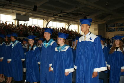 Graduates stand, waiting for the rest of their classmates to file inside the gym.