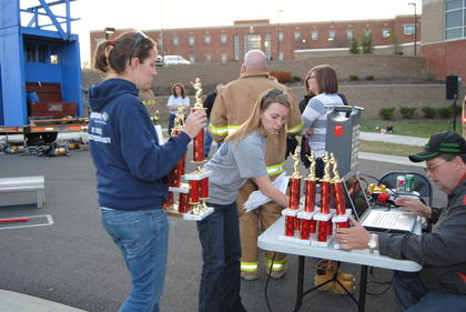 Olivia Helm and Ashley McWaters organize trophies. 