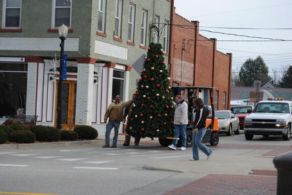 City of Hodgenville employees &quot;walk&quot; the new Christmas tree from the maintenance building to Lincoln Square.