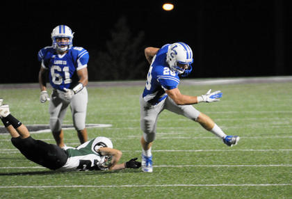 Cody Thompson slips past a tackle in the Hawks&#039; loss to North Bullitt. B.J. Carman is in back.