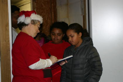 Santa&#039;s Helper Linda Daniels takes down names and ages of children.