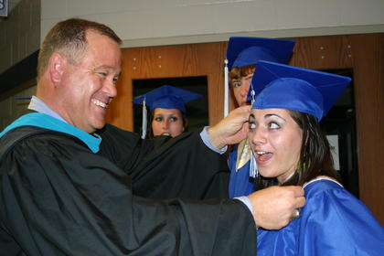 Principal Paul Mullins straightened Adrian Baumgardner&#039;s cap.