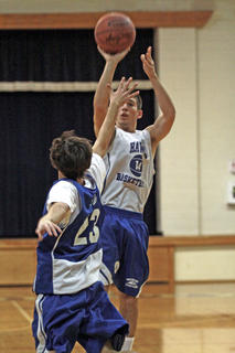 Kyle Meredith puts up a jump shot while Anthony Hall blocks.
