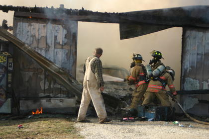 Lindon Nevins watched firefighters battle a barn fire at his son's home on Carter Brothers Road.