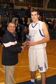 Sgt. Herberto Tua of National Guard presented junior Tyler Howell with a plaque for being named Player of the Game in the finals of the National Guard Holiday Classic.
