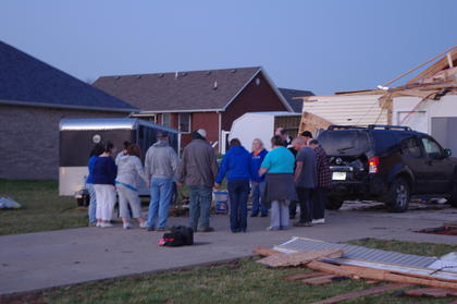 A family prayed together in front of a storm-damaged home in KC Estates.