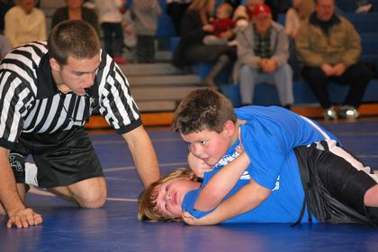 Referee Caleb Canter watches the progress of the match between Conner Lambert and Tanner LaFollette.