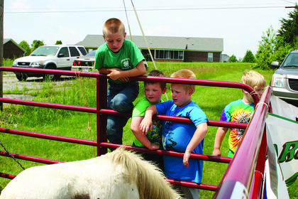 Jamie Grimes, Gabriel Rock, Kagan Rock and Devin Rock petted a miniature horse at Ag Market Day.