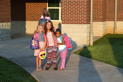 Brianna Hook, Adrianna Buckner and Zepplin Foreman pose for a first day of school photo in front of Abraham Lincoln Elementary School.