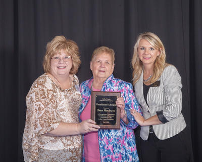 Past President, Allison Shepherd, left, and President Teleana Davis, far right, is pictured with Dean Henderson as she was recognized for her contributions and dedication of time and service to the Chamber.