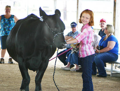 Natalie Gentry smiled as she showed her cow during the beef cattle novice showmanship division.