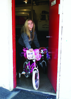 Volunteer Brittany Blair wheeled a new Barbie bike out of the Magnolia Firehouse.