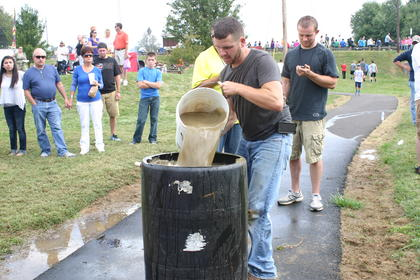 "Huey Thompson pours in the last bucket of water for ""Massey's Gang"" during the bucket relay"