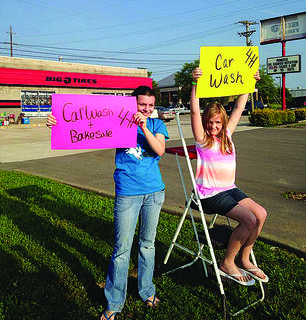 The 4-H Rabbit Club held a car wash to raise money to attend the national convention in Texas this fall. Sara Duvall and Janie Gilliam held signs to lure customers