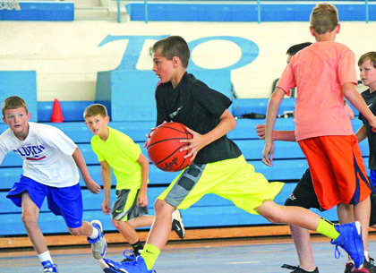 Daniel Snodgrass went in for a shot while Evan Morris and Kellen Bowen gave chase at Future Hawks Basketball Camp.