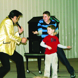 Caleb Brown, an Elvis tribute artist, sang and danced with children during the show. In back is Austin McClure.
