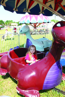 Farrah Kisselbaugh, age 3, enjoyed her ride on the dinosaur during the LaRue County Fair Kids Day Friday.