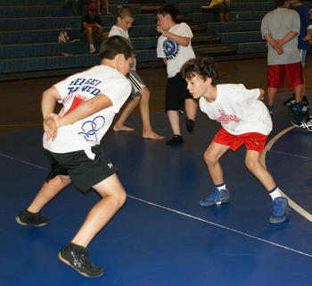 "Thomas Boone, left, and Gabe Fortier, played ""foot tag"" as part of their conditioning at wrestling camp."
