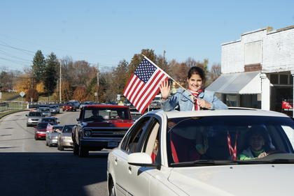 Susie Mohamed waved the flag while riding in the Veterans Day Parade with her sister Summer and friend, Diane Skaggs Obsorne. The Osborne family entered the event in honor of her father, J.D. Skaggs, a U.S. Army World War II veteran.