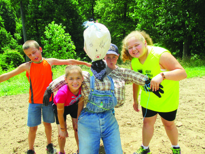 Heath Thompson, Maleah English, Patrick Butterworth, and AJ English pose with a scarecrow they made to guard the garden they planted.