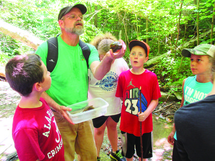 Earth Campers Kaden Burd, Patrick Butterworth, and Heath Thompson share a find with camp director Bob Ernst.