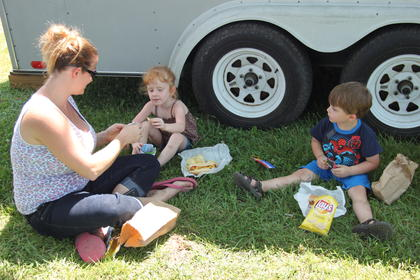 Lora and Haleigh Carman with J.D. Eggleston sought shade to enjoy their lunch in on Kids Day Friday at the Fair.