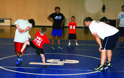 Landon Packard (kicking) tried to get the best of Connor Lambert during a game of foot tag in Wrestling Skills Camp. Watching the action are coaches Damon Barnes, Elijah Zwiep and Jason Detre.