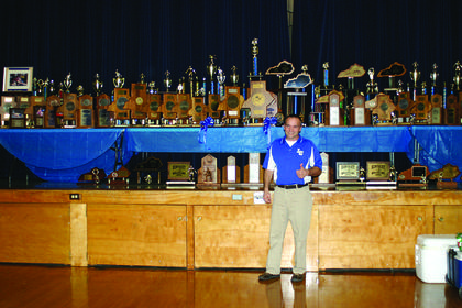 Long-time LaRue County High School Wrestling Coach Gary Canter posed with a few of the trophies his team has acquired over the years.