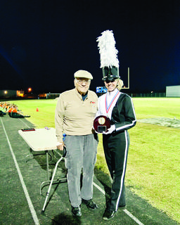 Former LaRue County Band Director Gene Hoggard presented the grand champion trophy to Adair Countys band at the Lincoln Days Marching Invitational Saturday. Eight bands competed on Hawk field.