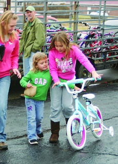Gracie Meredith, 10, and Charity Meredith, 4, pushed a new bicycle to the familys car.